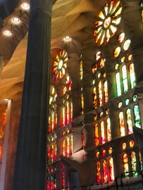The stained-glass windows from the Passion side reflect reds and oranges through the church